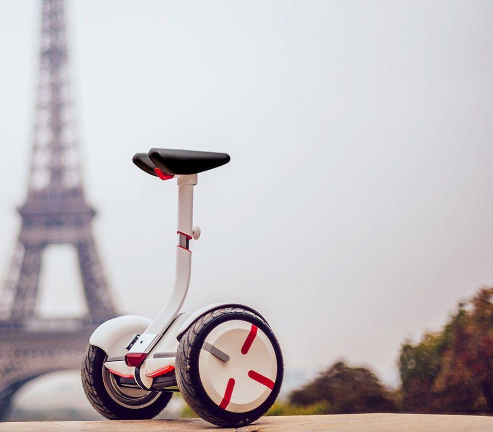 Самобалансирующейся скутер Ninebot mini Pro на фоне Эйфелевой башни